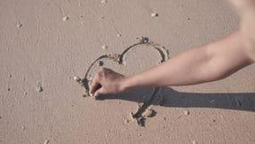 Coração do close-up na areia A mão do ` s da mulher tira um coração vídeos de arquivo