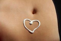 Coração do creme no estômago bronzeado Imagem de Stock Royalty Free