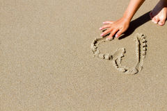 Coração do desenho da mão na areia Imagem de Stock