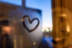 Coração do desenho na janela no inverno imagem de stock royalty free