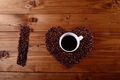 Coração do feijão do copo e de café fotografia de stock royalty free