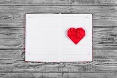 Coração do origâmi do papel vermelho Abra o caderno com páginas limpas e um coração de papel Moldes e fundos Imagem de Stock