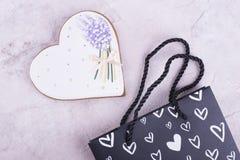 Coração do pão-de-espécie perto do pacote preto Fotos de Stock Royalty Free