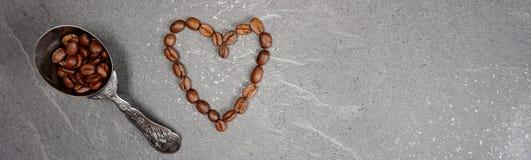 Coração dos feijões de café dos feijões de comércio justos com a colher no fundo cinzento do worktop da cozinha fotografia de stock