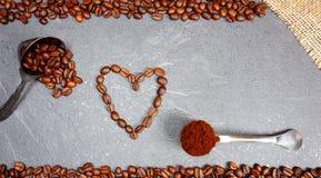 Coração dos feijões de café dos feijões de comércio justos com a colher no fundo cinzento do worktop da cozinha foto de stock royalty free