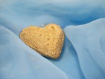 Coração dourado em um fundo azul imagem de stock royalty free
