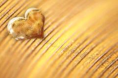 Coração dourado pequeno brilhante no pó do ouro Imagem de Stock