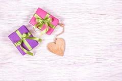 Coração e caixas de presente de madeira em um fundo branco Copie o espaço Caixas de presente brilhantes com fitas Imagem de Stock