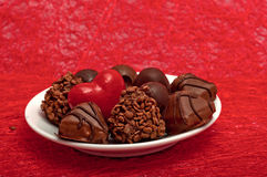 coração e chocolates vermelhos em uns pires brancos no sisal vermelho Fotografia de Stock Royalty Free