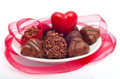 coração e chocolates vermelhos nos pires brancos Imagens de Stock