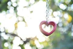 Coração e corrente de madeira vermelhos para o amor no fundo da luz solar e da natureza Foto de Stock Royalty Free