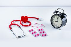 Coração e estetoscópio vermelhos, despertador, drogas, comprimidos na tabela fotografia de stock