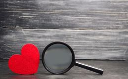 Coração e lupa vermelhos Conceito do amor e dos relacionamentos Busca para o amor Dia do `s do Valentim loneliness Encontre um do fotos de stock