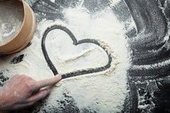 Coração e símbolo do amor, pintados na farinha, com mão de uma mulher fotos de stock