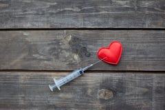 Coração e seringa vermelhos no fundo de madeira Toxicodependência concentrada Fotos de Stock Royalty Free