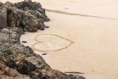 Coração em uma praia da areia com a rocha como o fundo Fotos de Stock