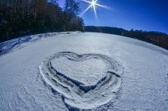 Coração esboçado na neve no lago Imagens de Stock