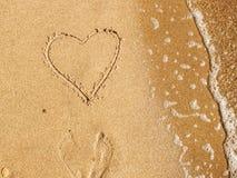 Coração escrito no Sandy Beach com a onda perto do mar Valentim feliz imagem de stock