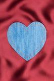 Coração feito da tela da sarja de Nimes com costura amarela na seda vermelha Imagens de Stock Royalty Free