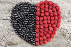 Coração feito das framboesas e dos mirtilos frescos no fundo de madeira Nutrição saudável Fotos de Stock