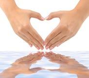 Coração feito das mãos e da água Fotografia de Stock