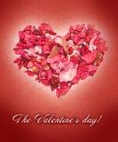 Coração feito das pétalas das rosas no fundo vermelho Fotografia de Stock Royalty Free