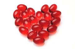 Coração feito de cápsulas vermelhas Fotos de Stock