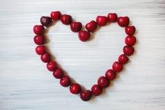 Coração feito de cerejas escuras Fruto vermelho no fundo de madeira O verão envia o amor Partículas da arte Fotos de Stock