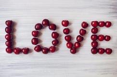 Coração feito de cerejas escuras Fruto vermelho no fundo de madeira O verão envia o amor Partículas da arte Imagem de Stock Royalty Free
