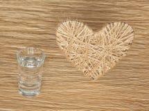 Coração feito do linho adornado com joias em um fundo da placa do carvalho Fotos de Stock