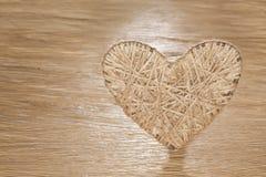 Coração feito do linho adornado com joias em um fundo da placa do carvalho Imagens de Stock