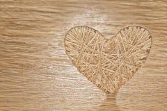 Coração feito do linho adornado com joias em um fundo da placa do carvalho Imagem de Stock