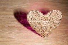 Coração feito do linho adornado com joias em um fundo da placa do carvalho Fotos de Stock Royalty Free