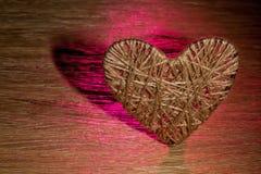 Coração feito do linho adornado com joias em um fundo da placa do carvalho Foto de Stock