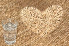 Coração feito do linho adornado com joias em um fundo da placa do carvalho Fotografia de Stock Royalty Free