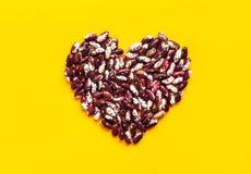 Coração feito dos feijões salpicados vermelhos e brancos crus secos no fundo amarelo brilhante Cartaz criativo da arte do aliment fotografia de stock
