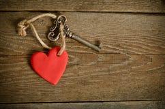 Coração feito a mão com chave em uma placa de madeira fotografia de stock royalty free