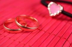 Coração folheado a ouro alaranjado com duas alianças de casamento Imagens de Stock
