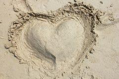Coração fora da areia em uma praia Imagens de Stock