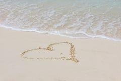 Coração na areia da praia com onda Foto de Stock Royalty Free