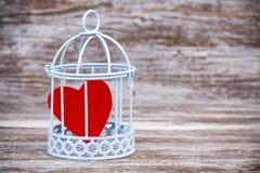 Coração na gaiola com fundo de madeira Fotografia de Stock