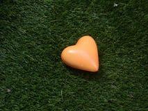 Coração na laranja no fundo da grama verde fotos de stock royalty free