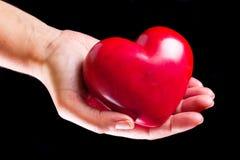Coração na palma sobre o fundo preto Fotografia de Stock