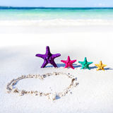 Coração na praia com estrelas do mar da cor Fotos de Stock