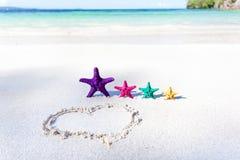 Coração na praia com estrelas do mar da cor Imagens de Stock Royalty Free