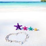 Coração na praia com estrelas do mar da cor Foto de Stock Royalty Free