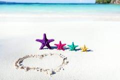 Coração na praia com estrelas do mar da cor Imagens de Stock