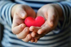 Coração nas mãos do ` s da criança Imagens de Stock