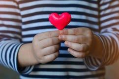 Coração nas mãos do ` s da criança Foto de Stock Royalty Free