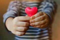 Coração nas mãos do ` s da criança Foto de Stock